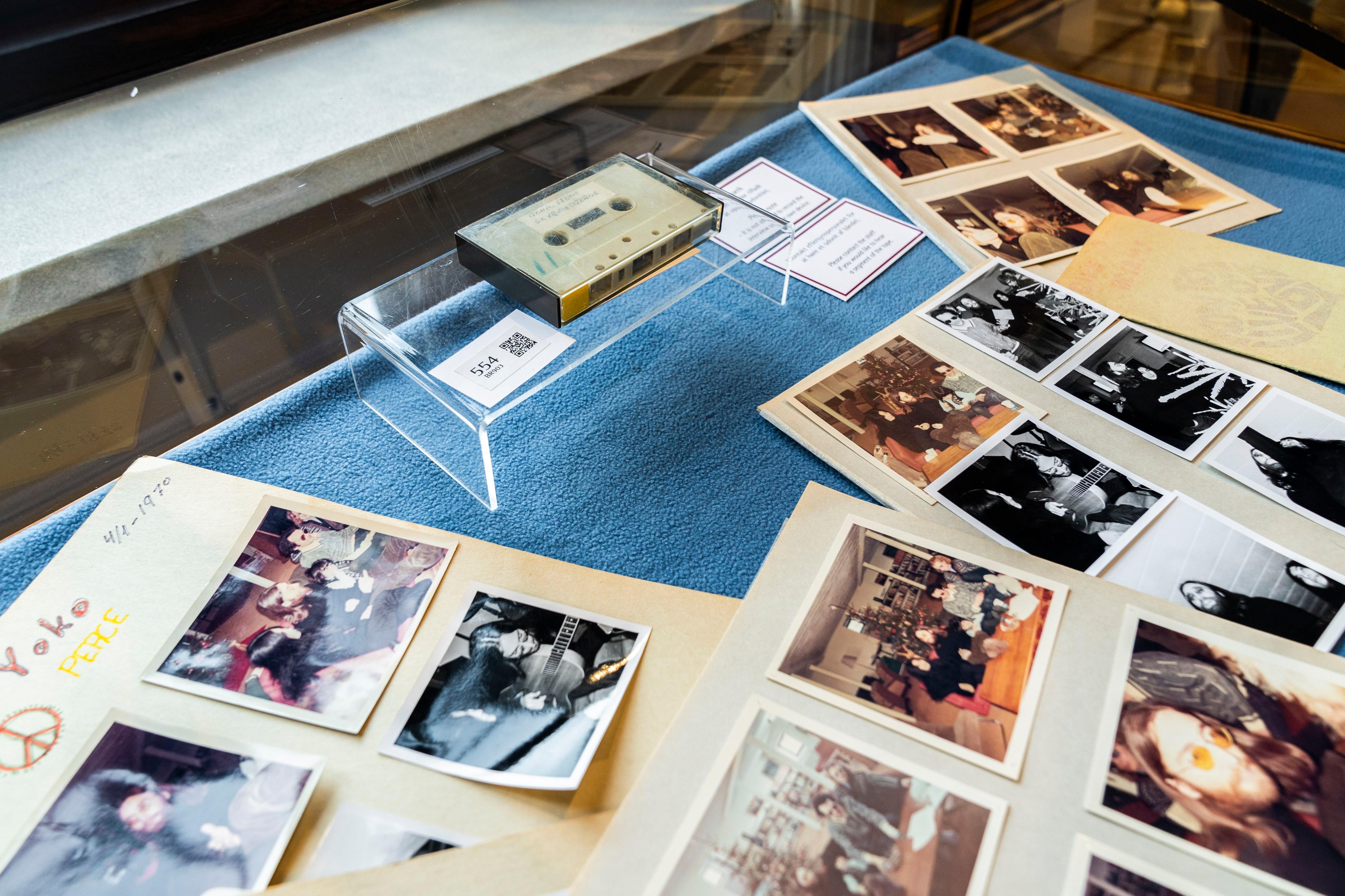 ARCHIVO - En esta foto del 24 de septiembre de 2021, un casete con una entrevista que cuatro chicos daneses le hicieron a John Lennon y Yoko Ono en 1970 se exhibe junto a varias fotografías en la casa de subastas Bruun Rasmussen en Copenhague. El casete se vendió el martes por 370.000 coronas (58.240 dólares). (Ida Marie Odgaard/Ritzau Scanpix via AP, Archivo)